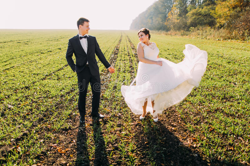 Lovely view of the newlyweds in the green field. The bride is playing with her wedding dress. stock photography