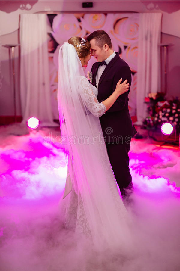 Lovely wedding couple dances in pink smoke.  royalty free stock images