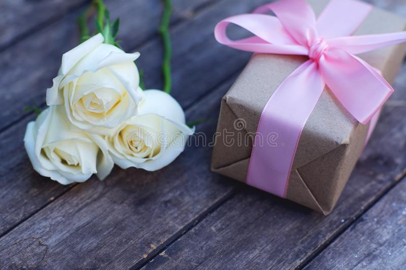 Lovely soft white color rose tied by pink ribbon and brown gift box on wood table background, sweet valentine present concept. Lovely white color rose tied by royalty free stock photography