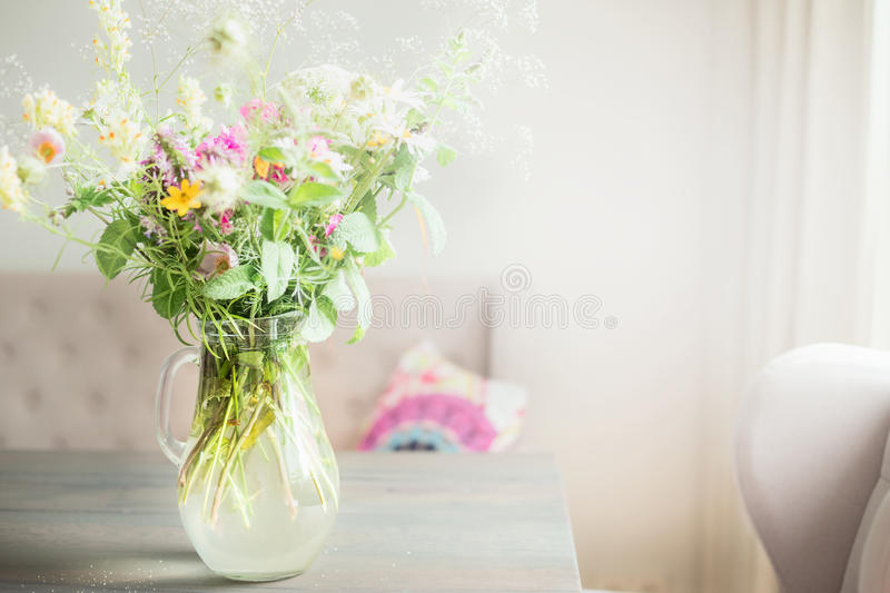 Lovely wild flowers bunch in glass vase on table in light living room , Home decoration stock photos