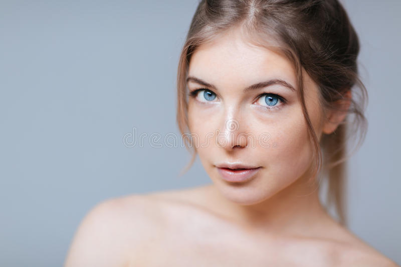 Lovely woman with fresh skin. Beauty portrait of a lovely woman with fresh skin standing over gray background stock photo