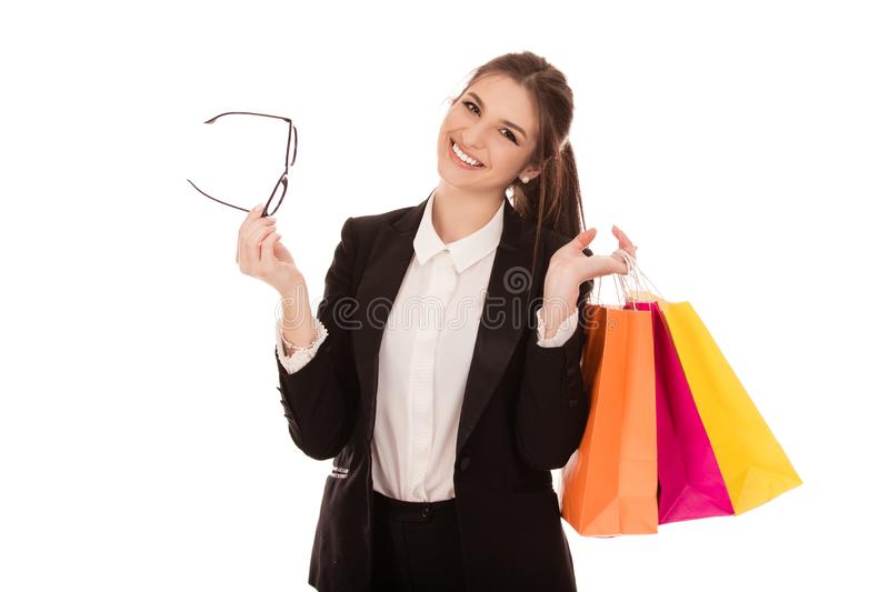 Lovely woman holding shopping bags and eye glasses. Lovely woman in formal wear holding multicolored shopping bags and eye glasses isolated over white background royalty free stock photography