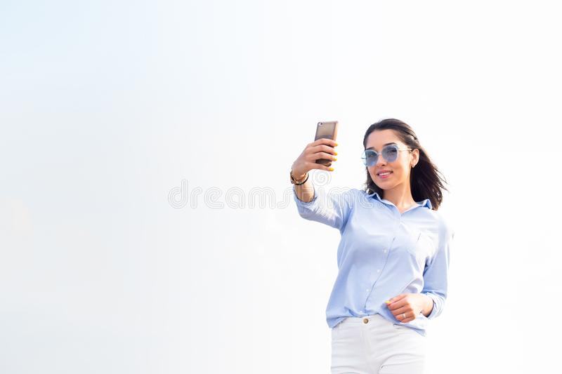 Lovely woman holding a smartphone and takes a selfie looks with a smile at the camera against the white sky on the street, horizon. Lovely woman holding a stock image