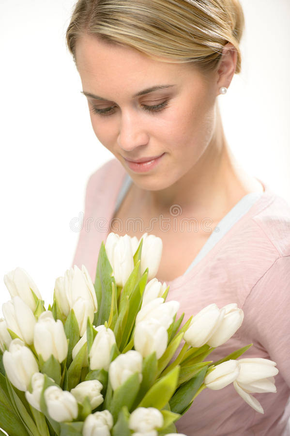 Lovely woman looking down white tulip flowers. Lovely woman looking down white spring flowers bouquet of tulips royalty free stock image