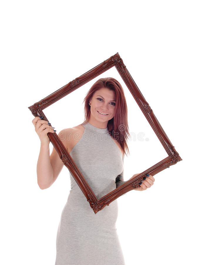 Lovely woman looking through frame. A beautiful young woman standing in a gray dress holding a picture frame, looking through, isolated for white background stock photography