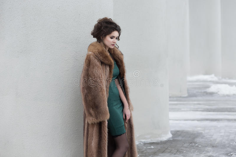 Glamour. Beauty Thoughtful Woman over White Wall in Wool Outwear dreaming royalty free stock image