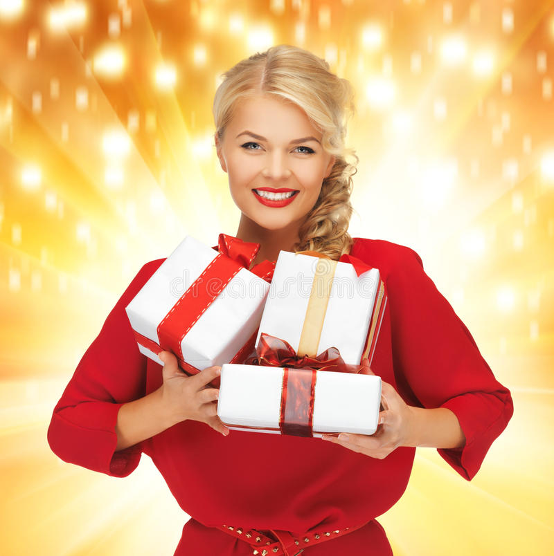 Lovely woman in red dress with gift boxes. Picture of lovely woman in red dress with gift boxes stock photo