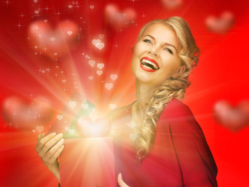 Lovely woman in red dress with valentine gift box. Picture of lovely woman in red dress with valentine gift box royalty free stock photography