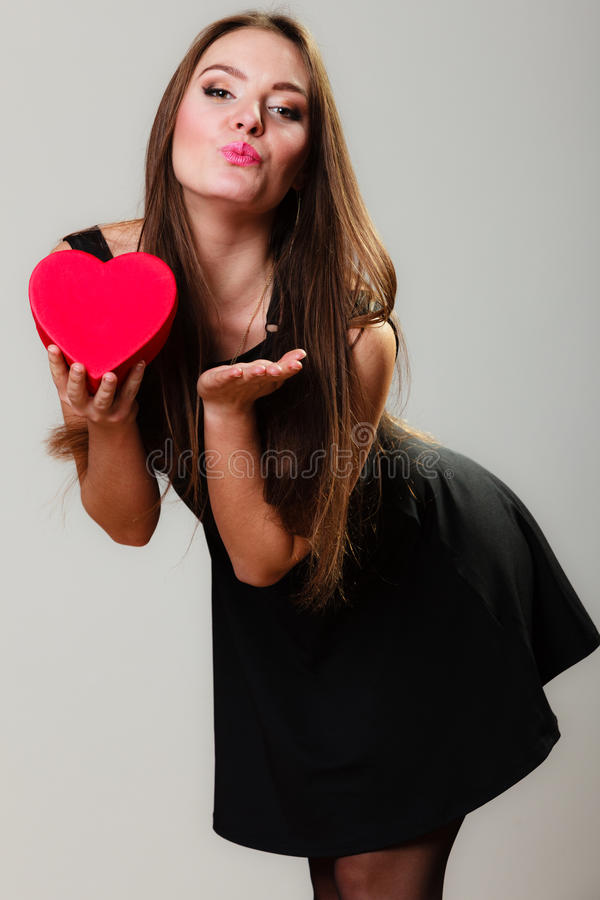 Lovely woman with red heart shaped gift box. Happiness, valentines day and love concept. Lovely elegant woman with red heart-shaped gift box blowing a kiss on stock photos