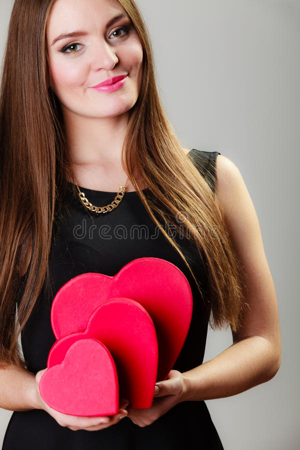 Lovely woman with red heart shaped gift boxes. Happiness, valentines day and love concept. Lovely elegant woman in black dress with red heart-shaped gift boxes stock images