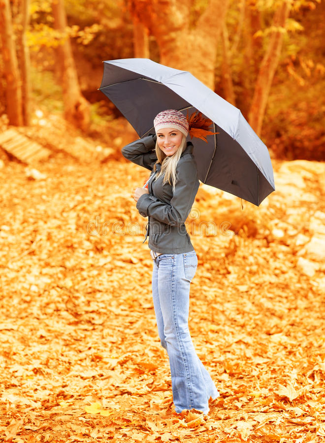 Lovely woman under umbrella. Photo of lovely woman walk under umbrella in rainy day in autumnal park, cute female holding dry tree leaves in hand, sweet girl royalty free stock image