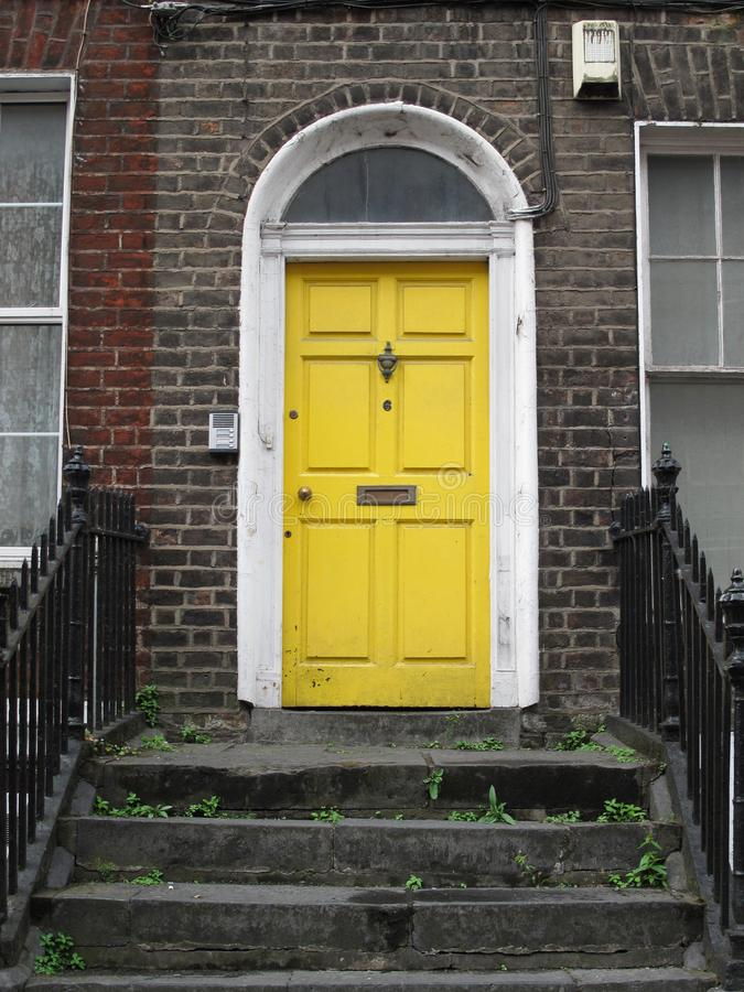 Lovely yellow door of a building in Georgian style in Limerick, Ireland royalty free stock photography