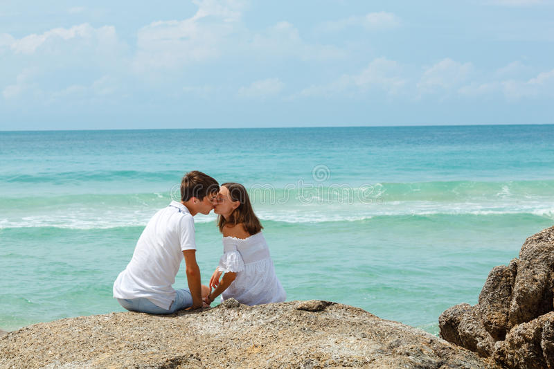 Lovely young adult couple on the rocks. Above tropical sea, back view stock image