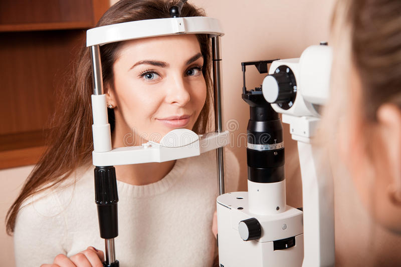 Lovely Young adult woman is having eye exam performed by eye doc stock images