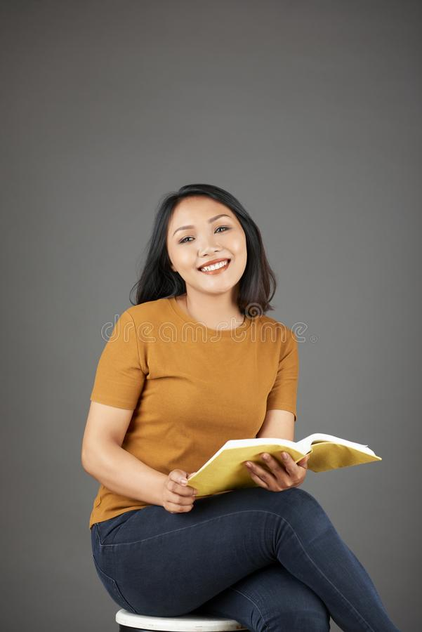 Lovely young Asian woman reading royalty free stock photo