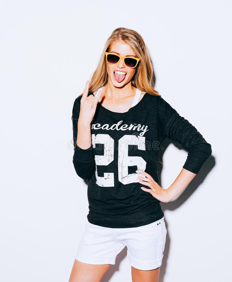 Lovely young blond woman making a call me gesture and showing tongue in suglasses, Sweatshirt and white shorts. White background. royalty free stock photos