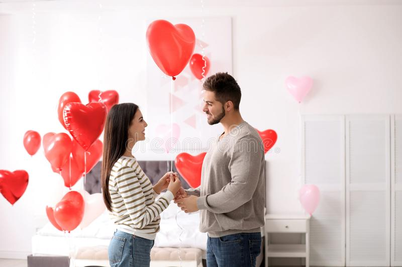 Lovely young couple in bedroom decorated with heart balloons. Valentine`s day celebration. Lovely young couple in bedroom decorated with heart shaped balloons stock images