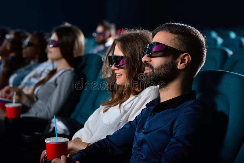 Lovely young couple on a date at the cinema royalty free stock images