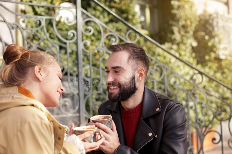 Lovely young couple enjoying tasty coffee on sunny day. Outdoors stock image