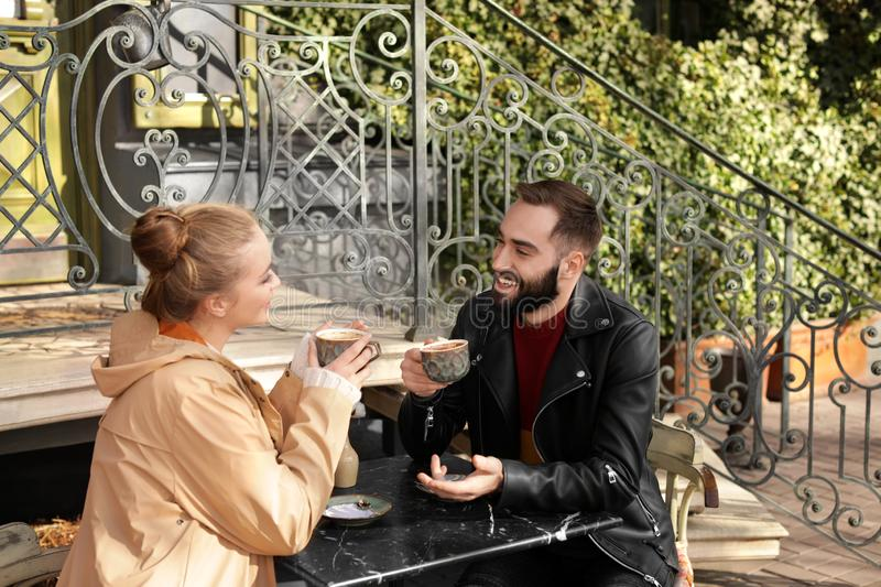 Lovely young couple enjoying tasty coffee at table. Outdoors royalty free stock photos