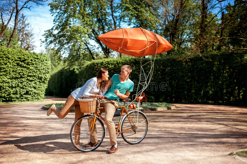 Lovely young couple having fun with the bicycle with red dirigible in the park in the summer royalty free stock photography