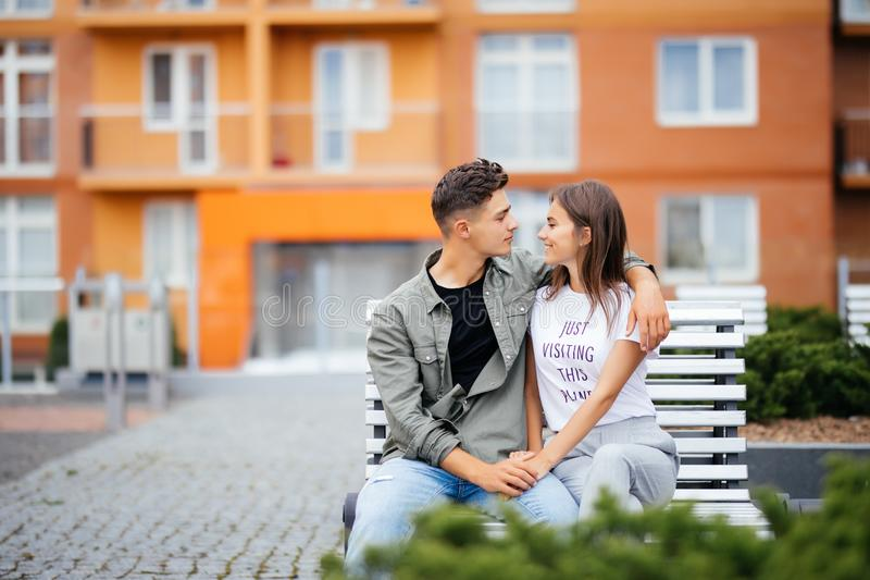 Lovely young couple in love in the park on a bench. Beautiful woman with long dark hair and a man hugging in the street. stock photography
