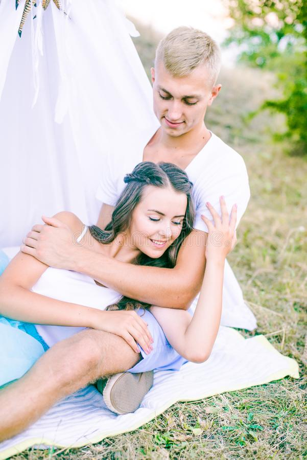 Lovely young couple in love in the summer in a field under a tree. Young couple enjoying each other in the summer stock photos