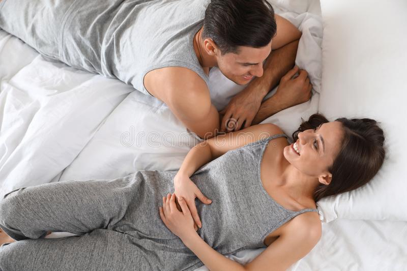 Lovely young couple resting on large bed, royalty free stock photo