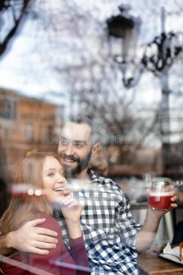 Lovely young couple spending time together in cafe, view through window stock images