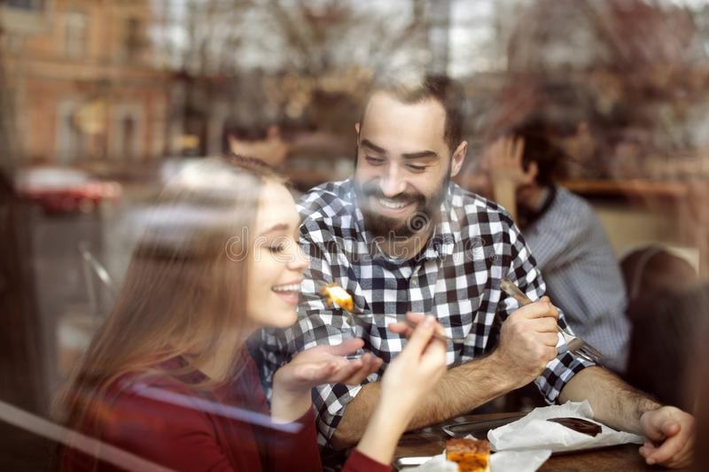 Lovely young couple spending time together in cafe. View from outdoors through window stock photography