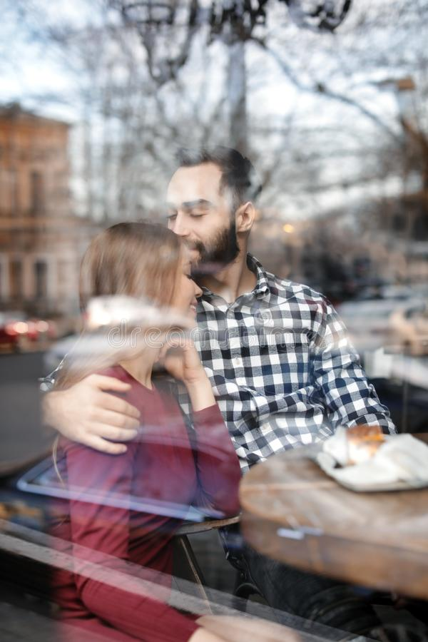 Lovely young couple spending time together in cafe, view through window. Lovely young couple spending time together in cafe, view from outdoors through window royalty free stock image