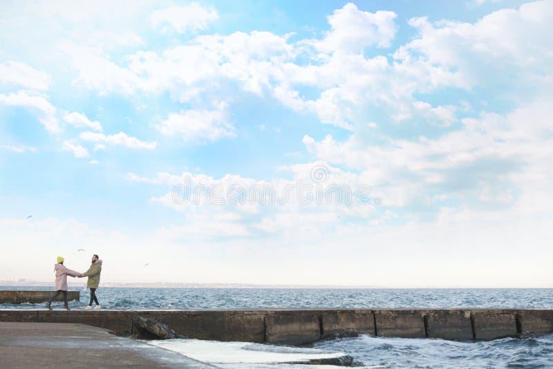 Lovely couple walking on pier near sea. Lovely young couple walking on pier near sea royalty free stock photo