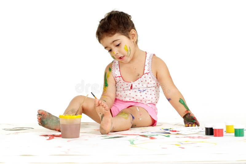 Lovely young girl draws painting while sitting on the floor on white stock photos