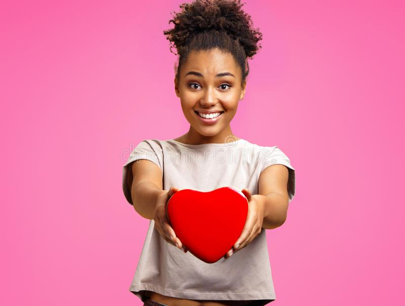 Lovely young girl holds heart shaped gift box. royalty free stock image