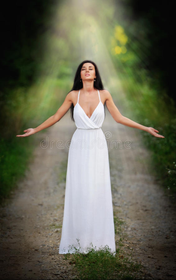 Lovely young lady wearing an elegant long white dress enjoying the beams of celestial light on her face in enchanted woods. Long. Hair brunette woman looking as stock photos