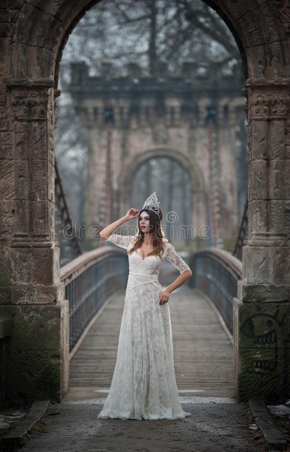 Lovely young lady wearing elegant white dress enjoying the beams of celestial light and snowflakes falling on her face stock images