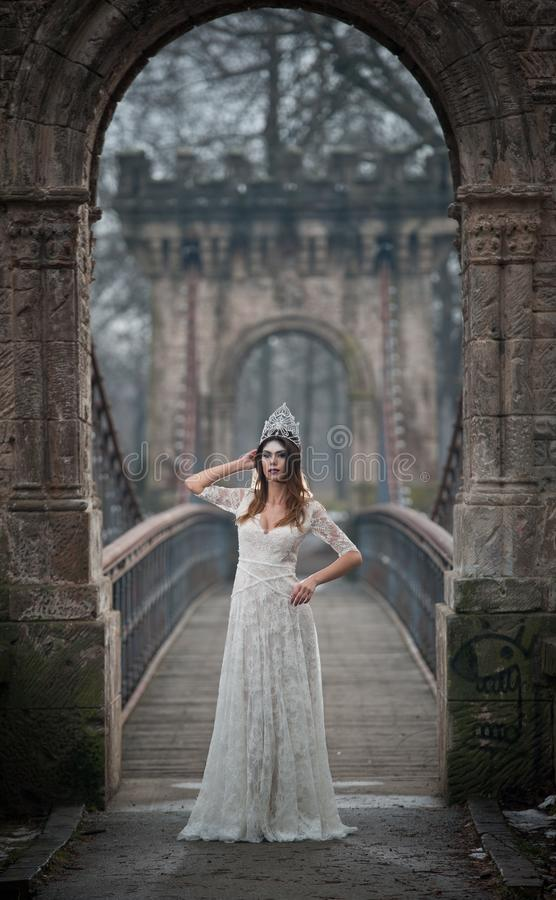 Lovely young lady wearing elegant white dress enjoying the beams of celestial light and snowflakes falling on her face royalty free stock photos