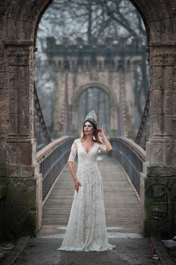 Lovely young lady wearing elegant white dress enjoying the beams of celestial light and snowflakes falling on her face royalty free stock photography