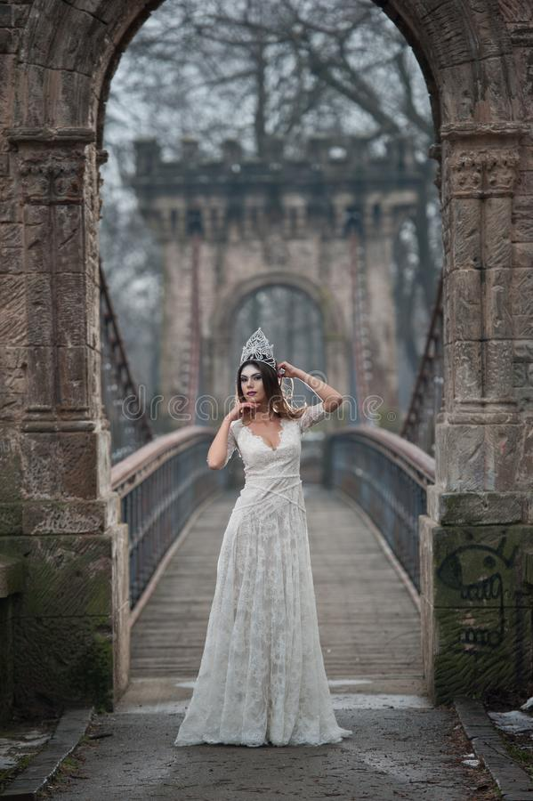 Lovely young lady wearing elegant white dress enjoying the beams of celestial light and snowflakes falling on her face stock photo