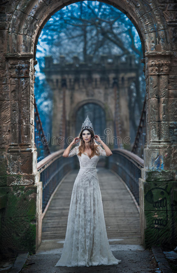 Lovely young lady wearing elegant white dress and silver tiara posing on ancient bridge, ice princess concept. Pretty brunette. Girl in long wedding dress stock images
