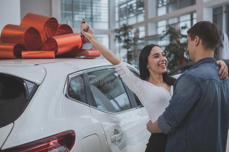 Lovely young married couple buying new car together. Excited young couple hugging, celebrating buying new automobile together at car dealership. Beautiful royalty free stock photo