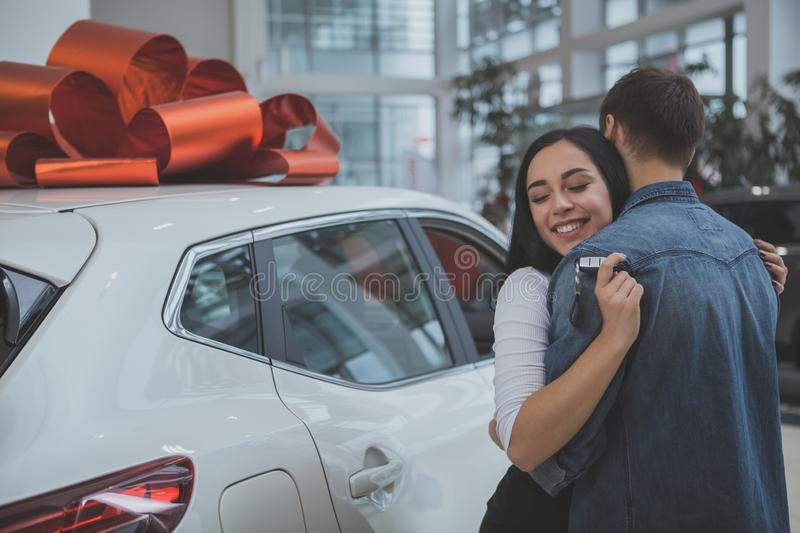 Lovely young married couple buying new car together. Gorgeous women hugging her husband, standing near new car with red bow on the roof. Loving men buying new stock images