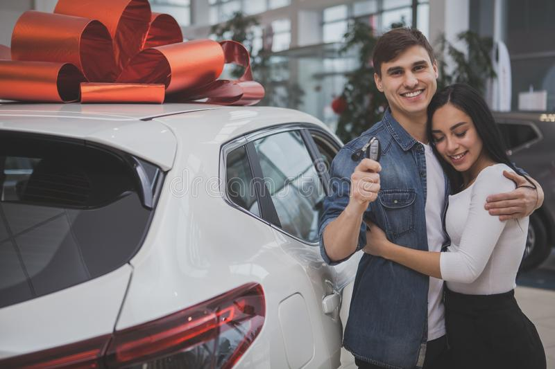Lovely young married couple buying new car together. Handsome happy men smiling joyfully, hugging his gorgeous girlfriend after buying new car at the dealership stock images