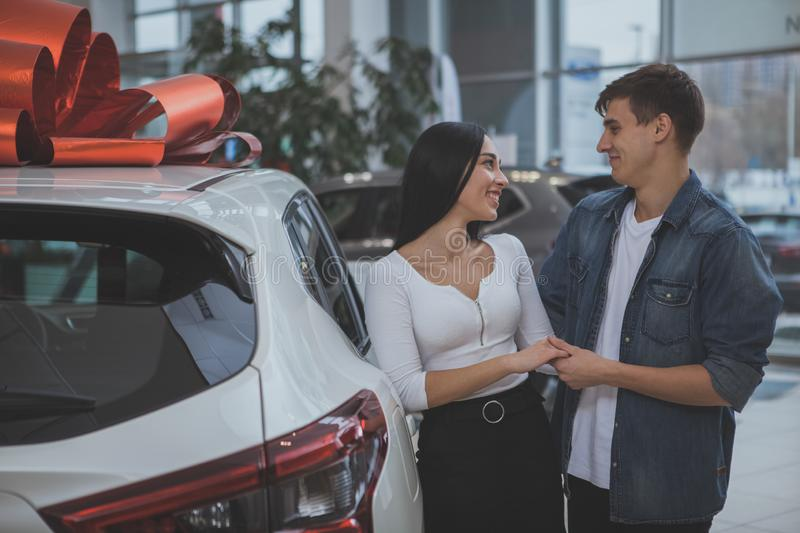Lovely young married couple buying new car together. Happy young couple holding hands smiling at each other while choosing new car at the dealership salon royalty free stock photography