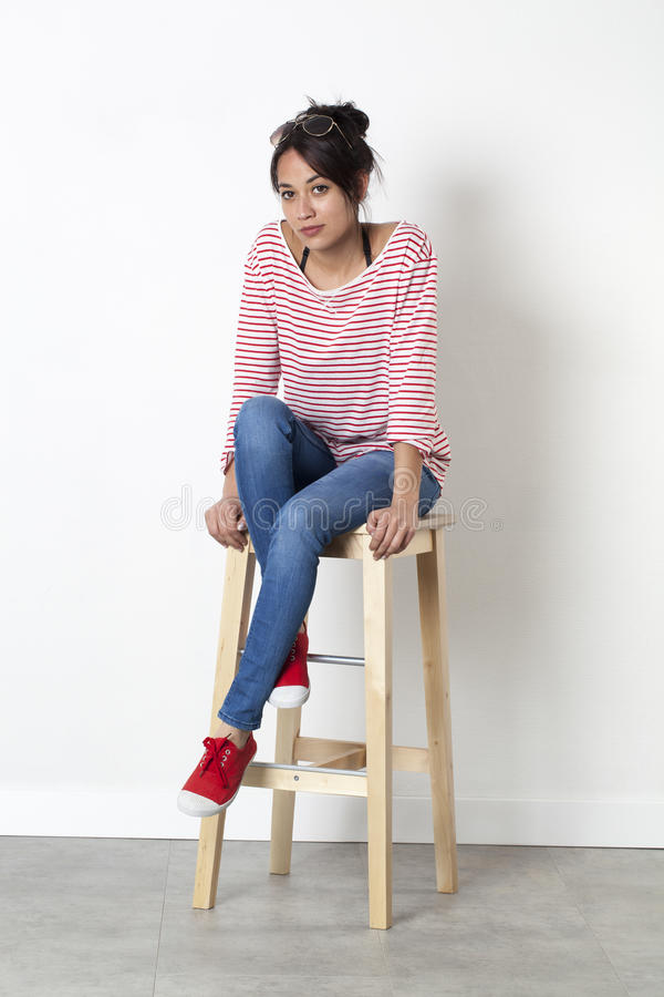 Lovely young multi-ethnic female student sitting on stool relaxing stock photo