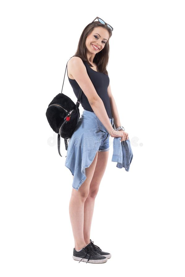 Lovely young stylish woman with plush bag and denim jacket tied around waist posing and smiling stock photo