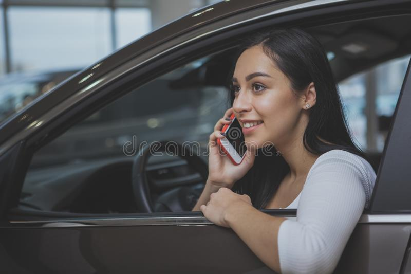 Lovely young woman buying new car stock photo
