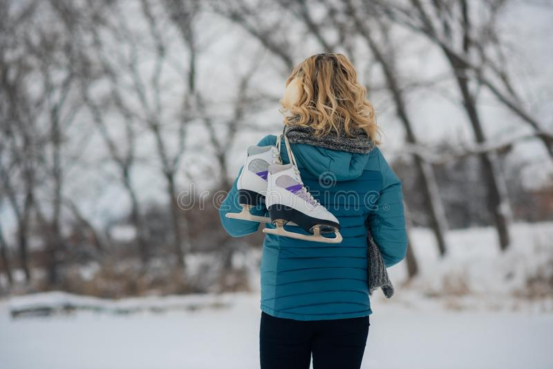 Lovely young woman girl with ice skates go to the rink royalty free stock image