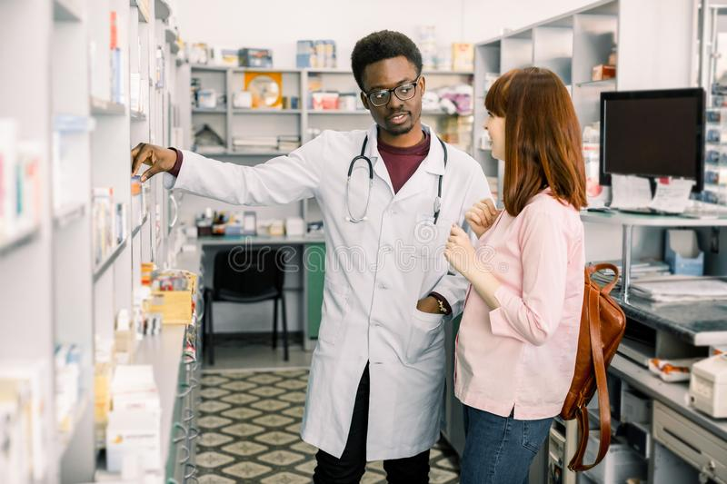 Lovely young woman smiling, buying medicines at the drugstore. African man pharmacist helping his female customer royalty free stock photo