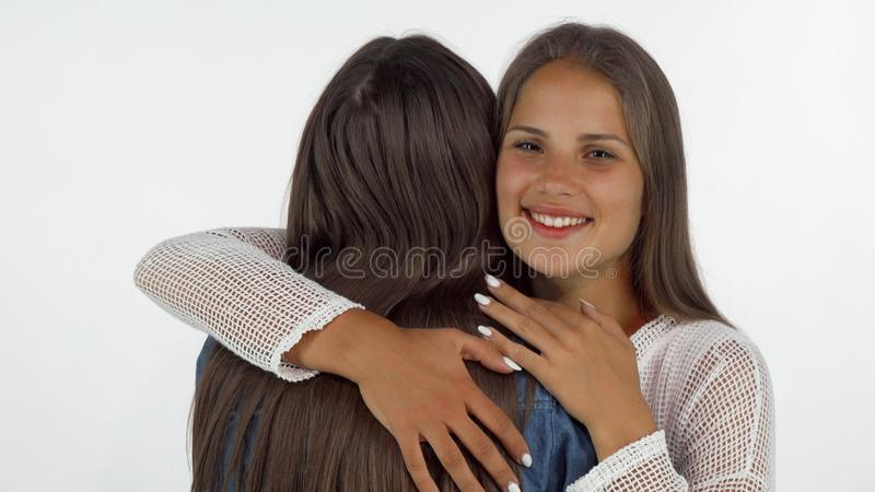 Lovely young woman smiling with eyes closed, embracing her best friend stock photos